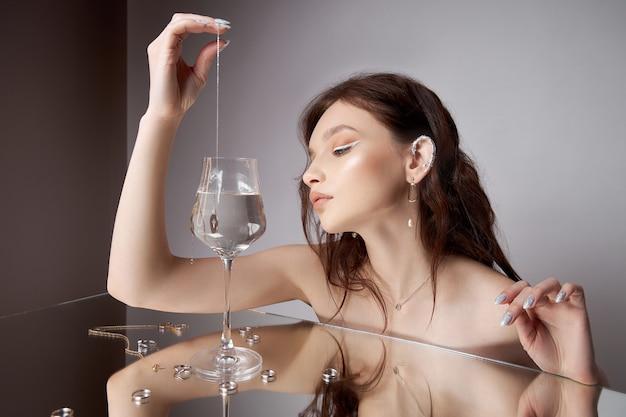 Bruinharige vrouw laat hanger met ketting in glas water vallen.