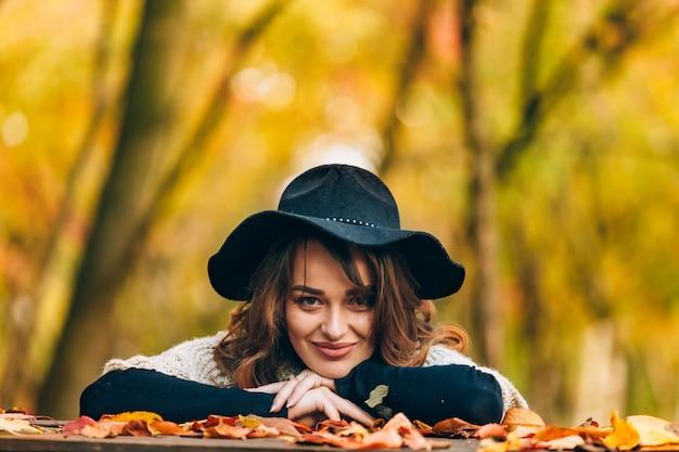 Bruinharige vrouw met hoed glimlacht en baseert haar handen op de tafel met gebladerte in het park
