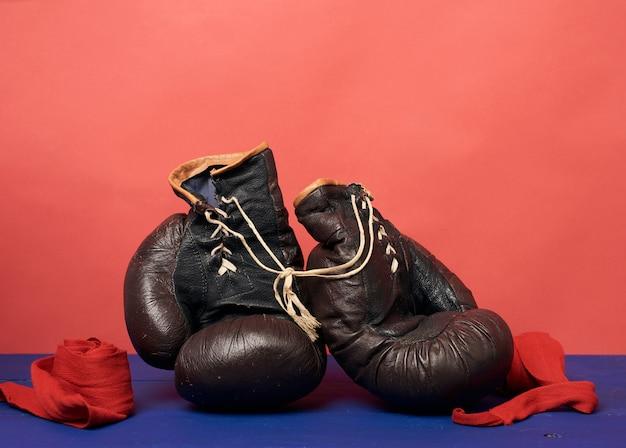 Bruinleren vintage bokshandschoenen op een rode achtergrond