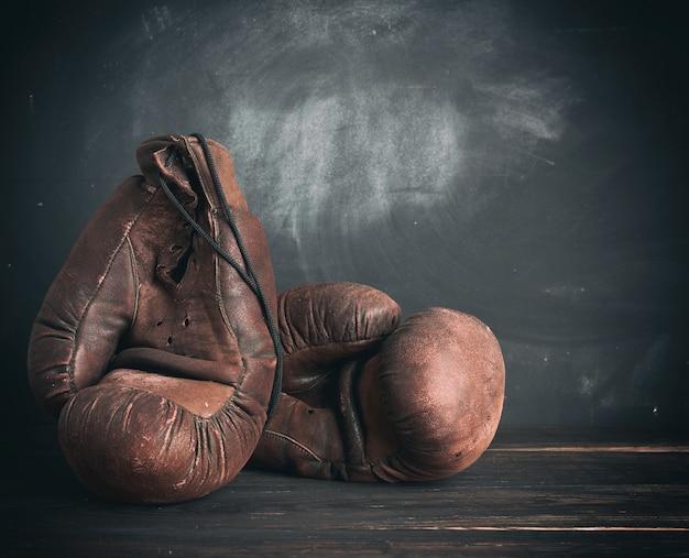 Bruinleren vintage bokshandschoenen op een zwarte achtergrond