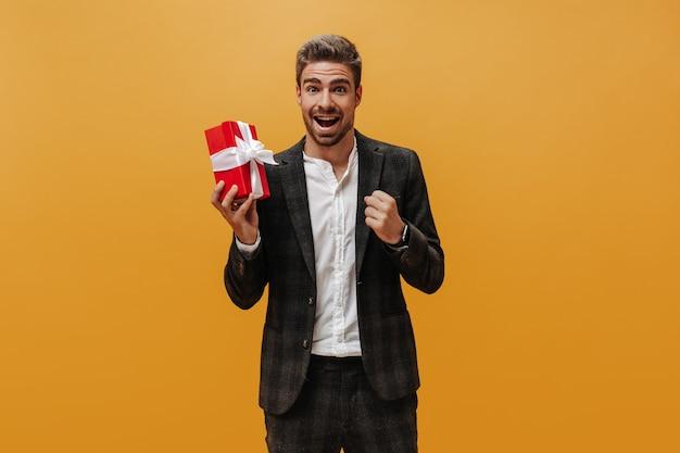 Bruinogige bebaarde man in geruit jasje, broek en wit overhemd verheugt zich, glimlacht en houdt rode geschenkdoos op oranje muur.