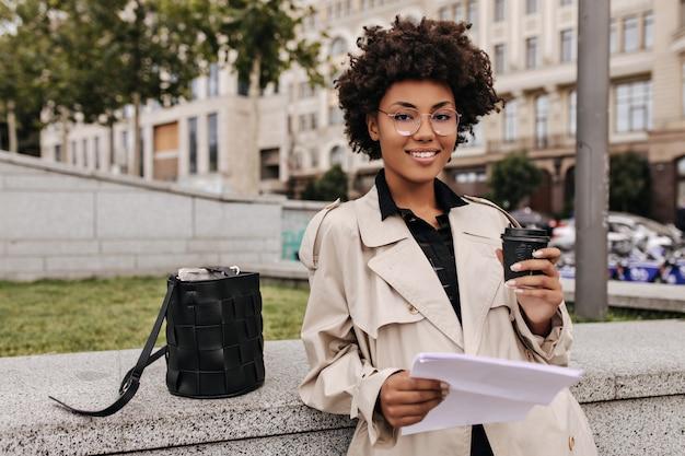 Bruinogige charmante brunette vrouw houdt koffiekopje vast