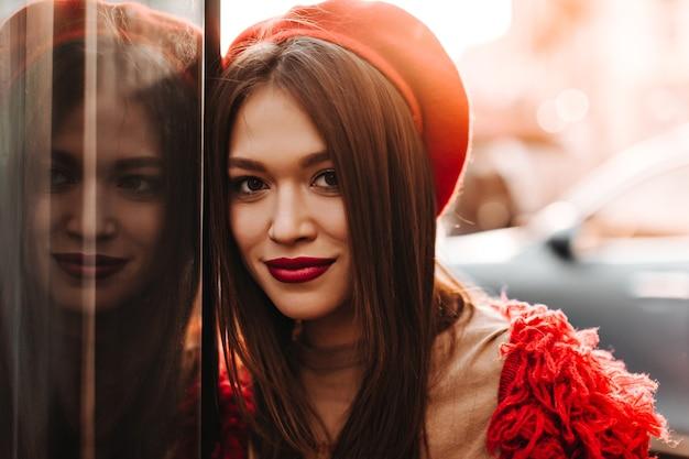 Bruinogige dame met gebruinde huid en rode lippen camera kijken, leunend op raam.