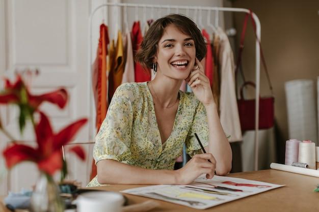 Bruinogige krullende brunette kortharige vrouw in trendy bloemenjurk glimlacht, kijkt naar de camera, sluit een potlood af en ontwerpt nieuwe kleding