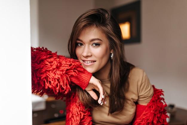 Bruinogige vrouw die met natuurlijke make-up camera bekijkt. stijlvolle dame in rood jasje en licht t-shirt kijkt naar de camera tegen de achtergrond van de kamer.