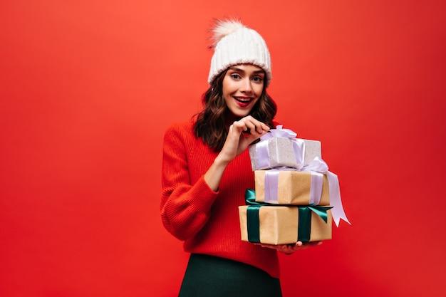 Bruinogige vrouw in rode trui en witte hoed opent geschenkdozen