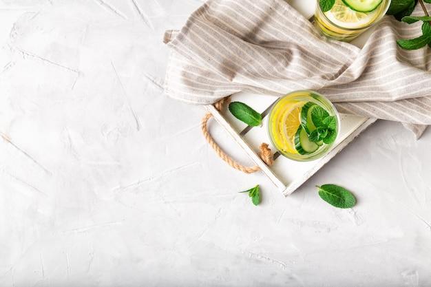 Bruisend water voor detox doordrenkt met citroen, komkommer en munt in glazen op houten dienblad op witte betonnen achtergrond. gezond levensstijlconcept. bovenaanzicht. ruimte voor tekst.