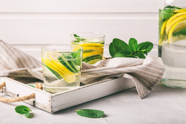 Bruisend water voor detox doordrenkt met citroen, komkommer en munt in glazen op wit houten dienblad. gezond levensstijlconcept.