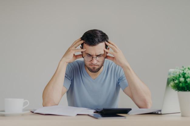 Brunet jonge man geconfronteerd met financiële problemen, niet in staat om hypotheek te betalen, heeft een wanhopige uitdrukking