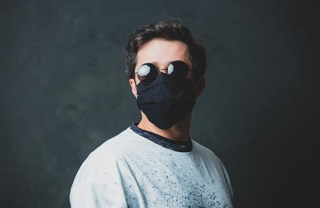 Brunet man in in zwarte gezichtsmasker en zonnebril op donkere muur