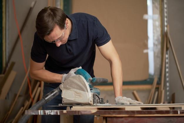 Brunet man werkt aan puzzel in werkplaats