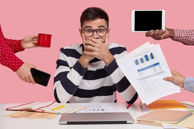 Brunet man zit aan bureau omringd met gadgets en papieren