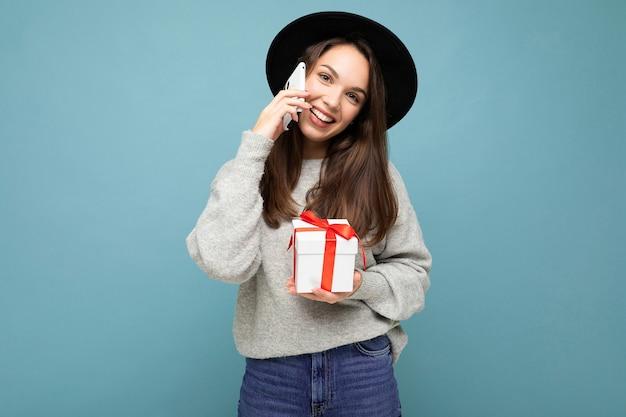 Brunet vrouw geïsoleerd op blauwe achtergrond muur dragen zwarte hoed en grijze trui houden geschenkdoos praten op mobiele telefoon en camera kijken.
