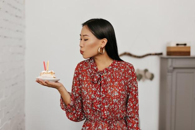 Brunette aziatische vrouw blaast kaarsjes uit op verjaardagstaart