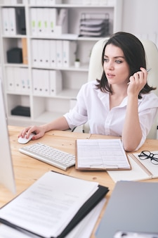 Brunette bankspecialist aan tafel zit en computer gebruikt tijdens het invullen van online formulier