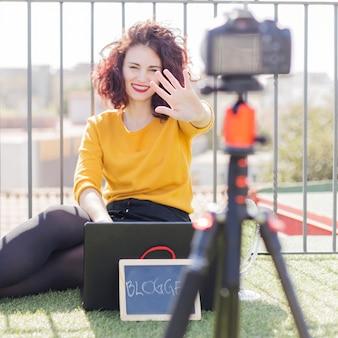 Brunette blogger die bord toont aan de camera