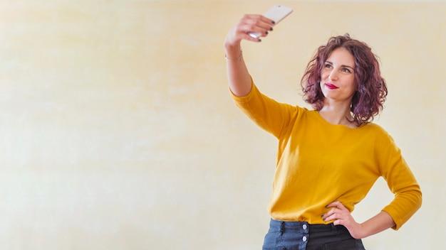 Brunette blogger die een selfie neemt