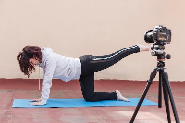 Brunette blogger die yogaroutine opneemt