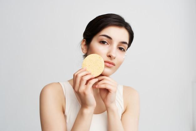 Brunette brengt een sponscrème aan op de schone huid van haar gezicht