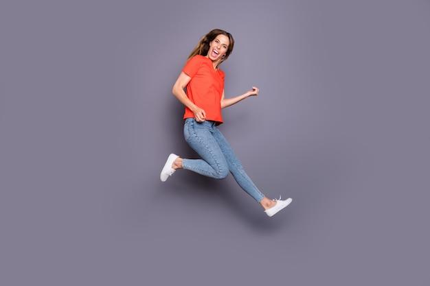 Brunette dame in rood t-shirt poseren en springen tegen de paarse muur
