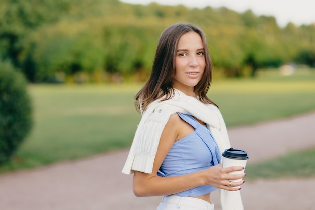 Brunette dame met slank lichaam, gekleed in t-shirt, witte trui op schouders, drinkt aromatische koffie