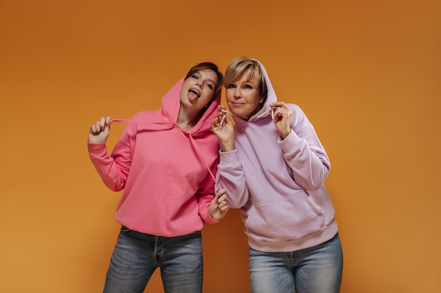 Brunette dame tong in roze kleding tonen en poseren met blonde vrouw in lila hoodies op oranje geïsoleerde achtergrond.