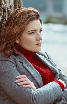 Brunette depressieve trieste vrouw bij de rivier in de stad op de achtergrond van de brug