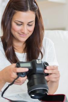 Brunette die foto's bekijkt terwijl het zitten op de bank