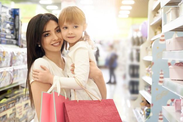 Brunette die kind op handen houdt en in opslag winkelt