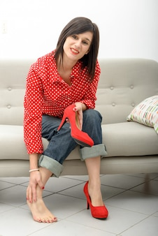 Brunette die pijn in voeten heeft na het dragen van schoenen met hoge hakken