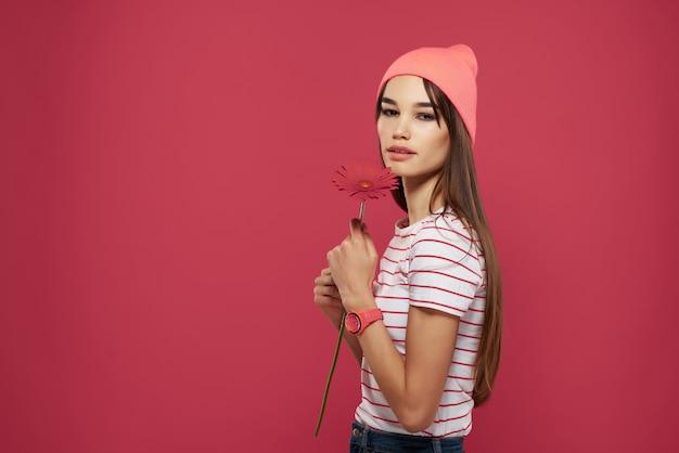 Brunette draagt een roze hoed rode bloem make-up decoratie roze achtergrond