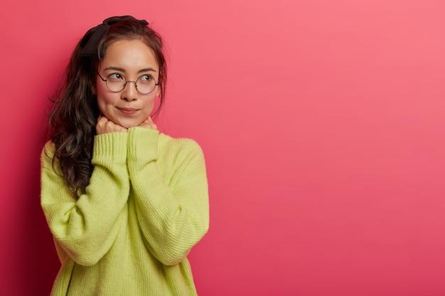 Brunette duizendjarige jonge aziatische vrouw houdt handen onder de kin, draagt een transparante bril