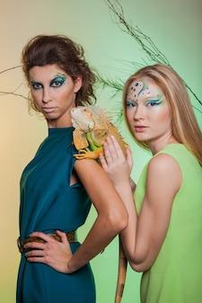 Brunette en blondine met een roofdierleguaan in hun handen. afbeelding van een vrouwelijk roofdier en een zachtaardig meisje met een dier in gevangenschap