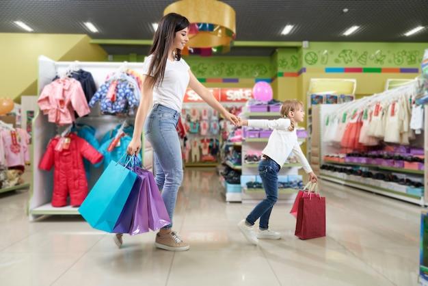 Brunette en schattig meisje winkelen in warenhuis.