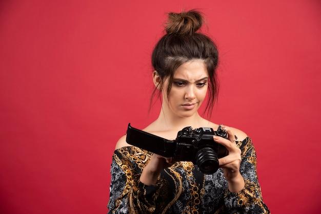 Brunette foto meisje controleert haar foto's in de camera en ziet er ontevreden uit.