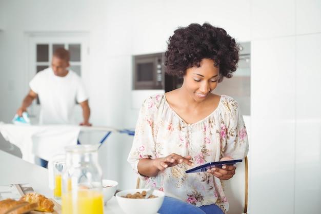 Brunette gebruikend tablet in keuken en haar vriend het strijken
