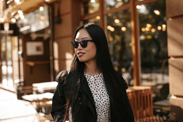 Brunette gebruinde aziatische vrouw in stijlvolle zonnebril, zwarte trenchcoat en witte blouse glimlacht