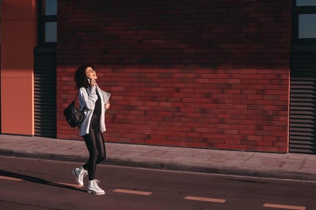 Brunette gekrulde student met een wandeling nadat de school op de telefoon spreekt en een laptop vasthoudt
