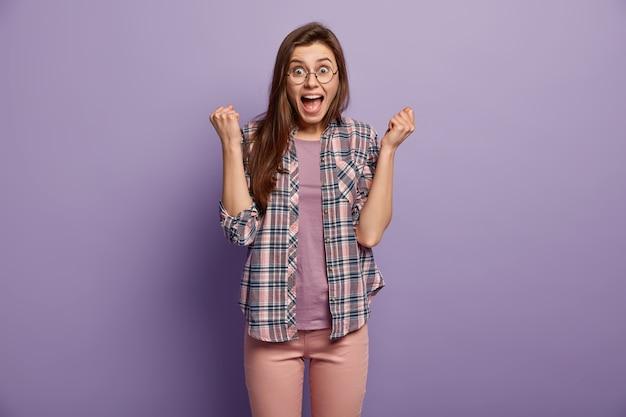 Brunette gelukkig meisje balde vuisten als winnaar, heeft dolgelukkig gelaatsuitdrukking verrast, houdt de mond open, draagt stijlvol geruit overhemd, poses en gebaren over paarse muur, behaalde de overwinning