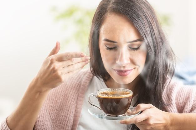Brunette geniet van de geur van vers gezette koffie in een kopje.