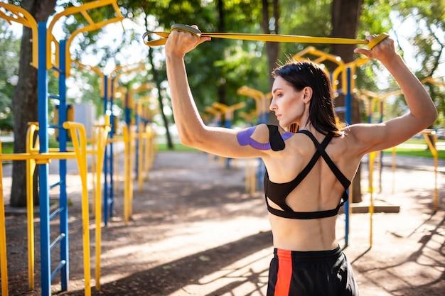 Brunette gespierde vrouw poseren met fitness weerstand band in park, sportveld op