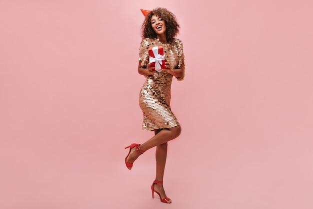 Brunette haired meisje in vakantie pet, stijlvolle hakken en moderne glanzende jurk met rode geschenkdoos op geïsoleerde roze muur..