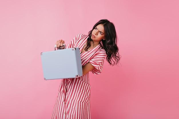 Brunette houdt een superzware tas vast en poseert emotioneel. meisje met golvend haar poseren in beweging.