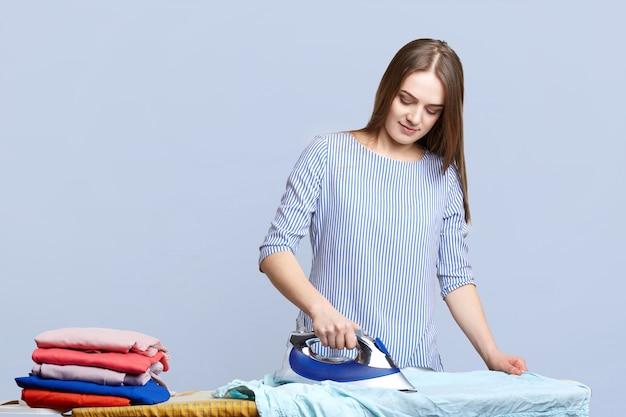 Brunette huisvrouw strijkt kleding op strijkplanken, schreeuwt het netjes, de hele dag bezig, doet huishoudelijk werk, geïsoleerd op blauw. vrouw met strijkijzer. huishoudelijk werk concept