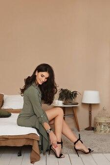 Brunette in een jurk zittend op het bed in de kamer en het aantrekken van zwarte schoenen op hoge hakken.