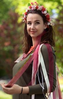 Brunette in een kaki jurk, een luxe krans met gekleurde linten en een heldere ketting