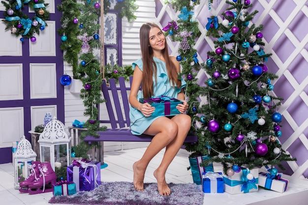 Brunette in een turquoise jurk zittend op een schommel