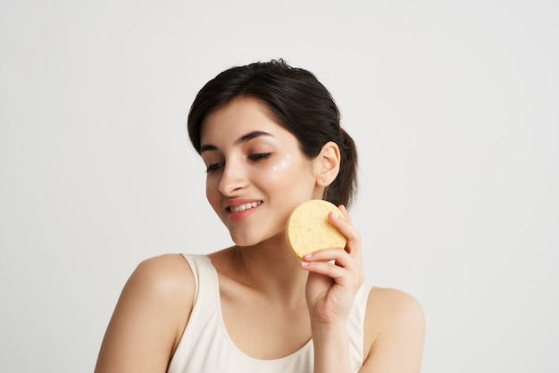 Brunette in een witte t-shirt met een spons in haar handen gezicht huidverzorging cosmetica