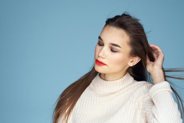 Brunette in een witte trui rode lippen charmeren lang haar blauwe achtergrond
