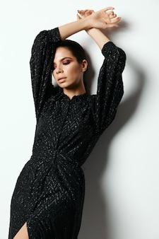 Brunette in een zwarte jurk ergens handen boven haar hoofd lichte make-up glamour mode.